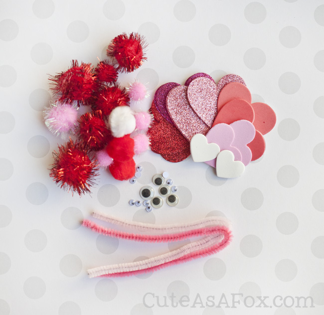 Love Bugs - a Valentine's Day kids craft. Common craft supplies like pom poms, pipe cleaners, foam, paper and googly eyes are all you need to create this cute and fun love bugs.